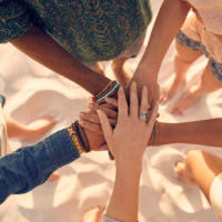 Group of young men and women showing unity. Group of young friends putting their hands together at the beach.