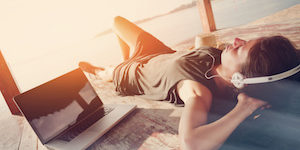 Young woman chilling with laptop and listening music with headphones in shadow shelter. Blurry effect, lens flares effect, intentional sun glare